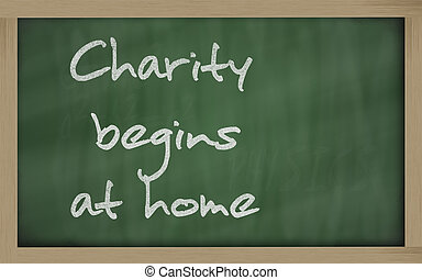 """ Charity begins at home "" written on a blackboard -..."