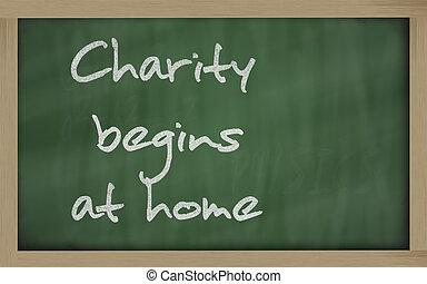 """ Charity begins at home "" written on a blackboard -..."