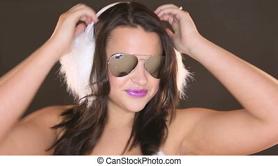 Dancing Woman In Sunglasses with arm raised and feathers in...