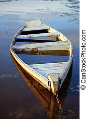Sinking boat - The flooded wooden boat on river bank