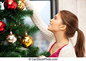 woman decorating christmas tree - bright picture of woman...