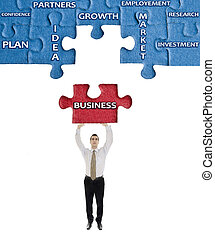 Business word on puzzle in man hands
