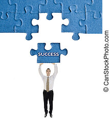 Success word on puzzle in man hands