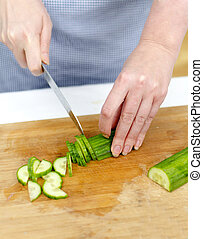 Womans hands cutting cucumber