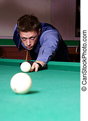 billiards table and man - portrait of a young man playing...