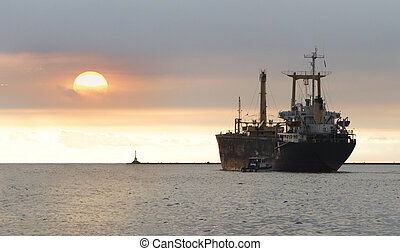 Cargo ship and tugboats at sunset