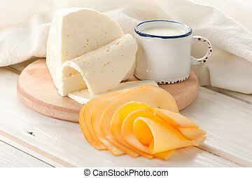 Breakfast with milk and cheese on old wooden table with...