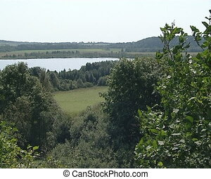 View from observation deck. Lake surrounded by forest and...