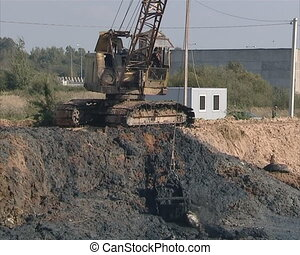 Excavator digging mud from ditch.