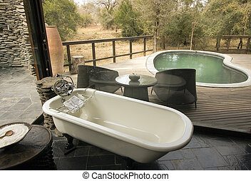 Bathroom view overlooking a pool and wooden deck at a lodge...