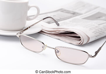 Eyeglass and newspaper - Morning paper with a cup of strong...