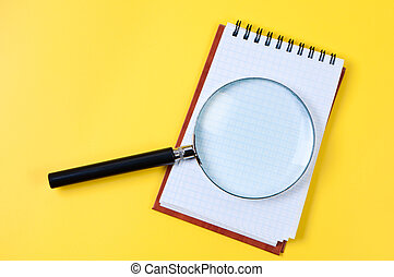 Magnifying glass and notepad on yellow background.