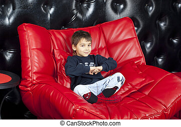 Kid on a red leather sofa
