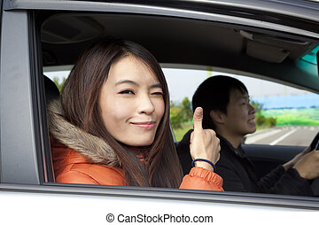 Happy smiling couple Driving in the car with thumbs up