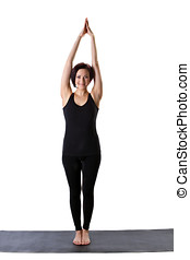 woman stand on rubber mat in yoga pose