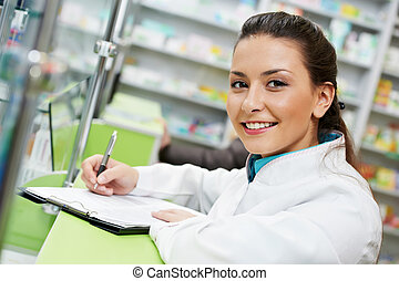 Pharmacy chemist woman in drugstore - cheerful smiling...