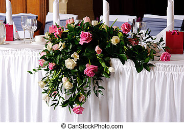 Head table at wedding reception decorated with flowers
