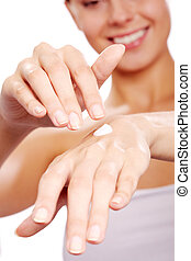 Applying handcream - Image of female hands being treated...