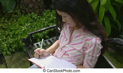 Attractive asian woman writes - An attractive young asian...