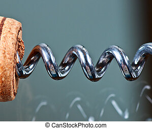 Corkscrew and cork on a glass table close up