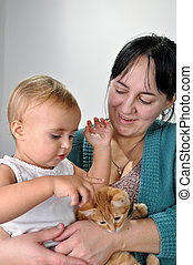 mother and daughter playing with a cat