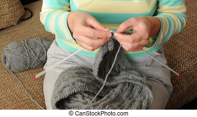 Two hands knitting with needles scarf