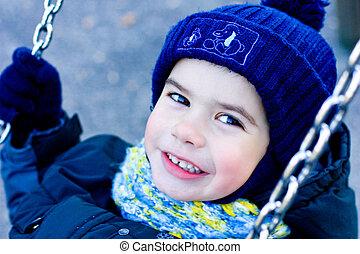 Portrait of cute  boy on swing