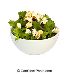 Bowl filled with salad and popcorn over white