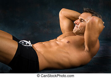 Man Exercising Situps - Athletic man performs situp...
