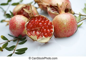 pomegranate - forefront of a pomegranate pieces on a white