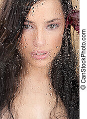 woman's face behind glass full of water drops - Close up of...