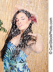 enjoying under shower - young woman with orchid in her hair...