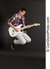 Young male jumping with guitar - Photo of a teenage male...