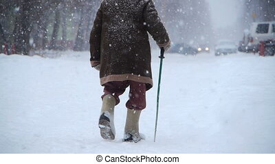 elderly man walks at winter street