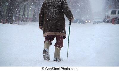 elderly man walks at winter street