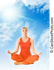 Beautiful young woman meditating in the sky