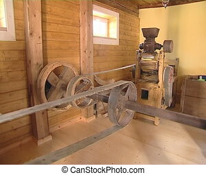 Old mill equipment. Human hands turn machines. Grain milling...