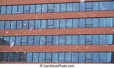 Snowfall against an office building
