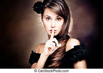 secret - beautiful young woman gesturing silence, studio...
