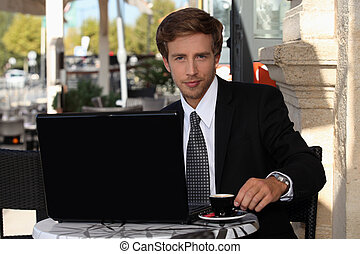 Young businessman having coffee outdoors