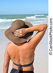 Attractive Woman on the Beach Holding Her Hat