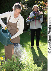 Young woman gardening with her grandmother