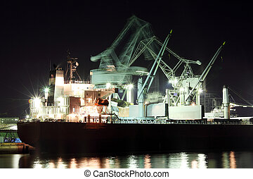 boat in a port - port with large cranes and cargo ship at...