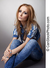 Beautiful girl sit in jeans and jacket