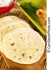 Indian flatbread called chapati on wooden board Selective...