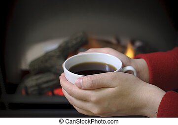 Holding coffee in fornt of fireplace