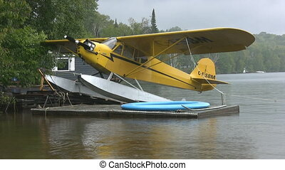 Seaplane in the rain. Two shots. - Two shots of a yellow...
