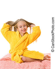 Pretty young girl sitting on a bed and touching her hair