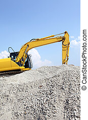 yellow digger - Yellow digger resting on a earth pile