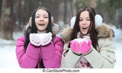Blowing and throwing snow - Two girls blowing then throwing...
